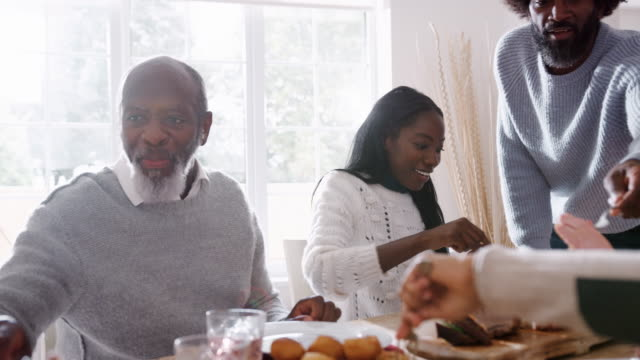 Multi-generation-mixed-race-family-sitting-at-the-table-serving-each-other-Sunday-dinner-at-home-close-up-backlit