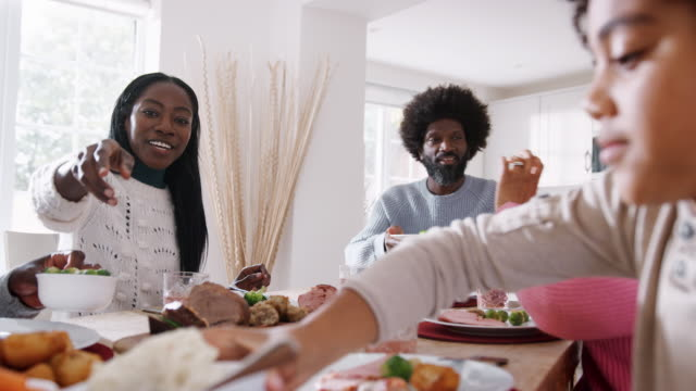 Multi-generation-mixed-race-family-sitting-at-the-table-serving-Sunday-dinner-at-home-close-up-low-angle