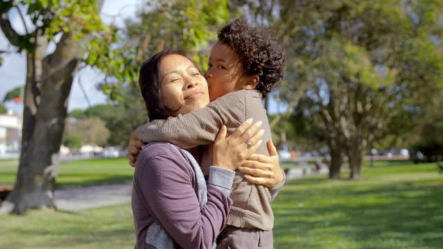 Geschweiften-afroamerikanischen-Sohn-umarmen-und-küssen-Mutter