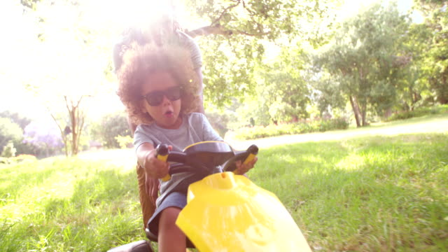 Handsome-African-American-father-and-son-playing-with-a-pedal-car