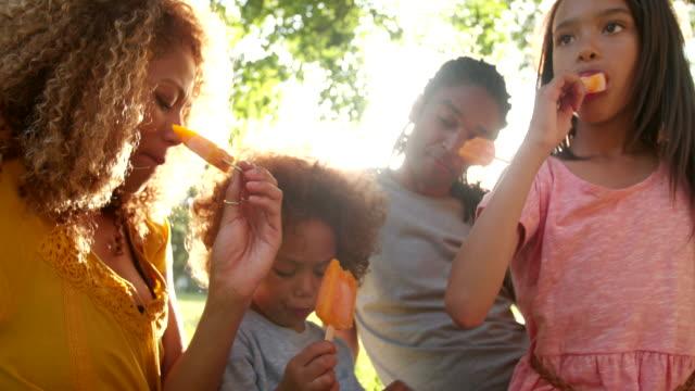 Pareja-joven-atractiva-comer-helado-en-el-sol-con-los-niños