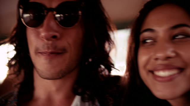 Happy-young-couple-enjoying-a-road-trip-with-friends