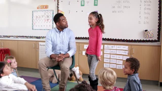 Hispanic-Schulkind-Nur-Mädchen-stehend-mit-Lehrer-in-der-Klasse-vor
