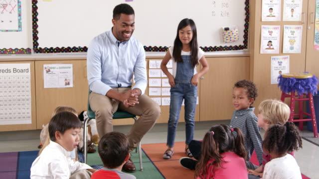 Asian-schoolgirl-standing-with-teacher-in-front-of-class