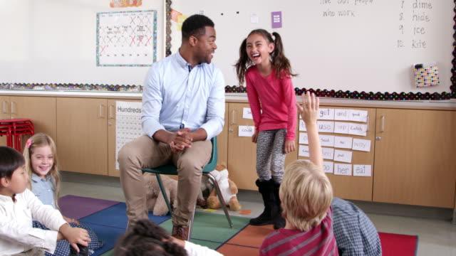 Niña-en-edad-escolar-hispana-de-pie-con-profesor-en-frente-de-la-clase