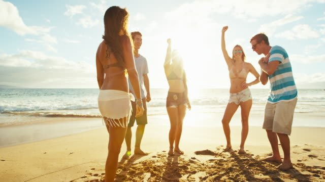 Group-of-friends-hanging-out-on-the-beach-at-sunset