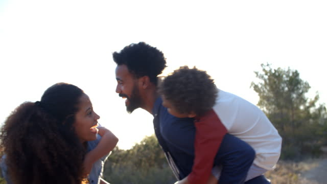 Parents-giving-their-kids-piggybacks-outdoors-waist-up