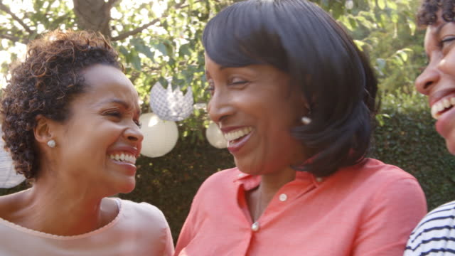 Black-mother-and-adult-daughters-talking-in-garden-close-up