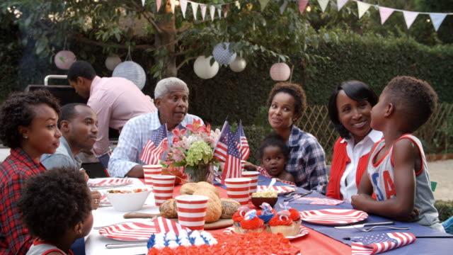 Multi-familia-de-generación-negro-hablando-en-barbacoa-el-4-de-julio