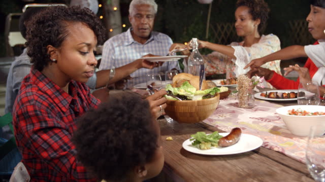 Multi-generation-black-family-serving-food-at-table-outdoors