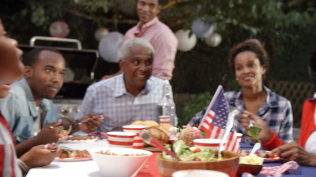 Two-young-black-boys-stand-to-entertain-family-at-a-barbecue