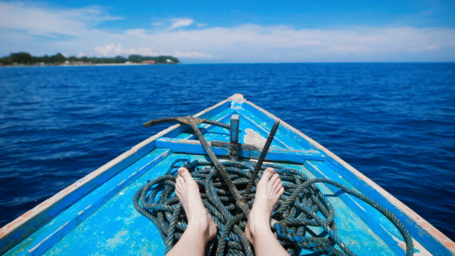 Ocean-island-of-Bali-Boat-tour-Young-man-in-a-boat-on-the-ocean-excursions-Stunningly-clear-ocean-year-round-sunshine-paradise-island---idyllic-picture