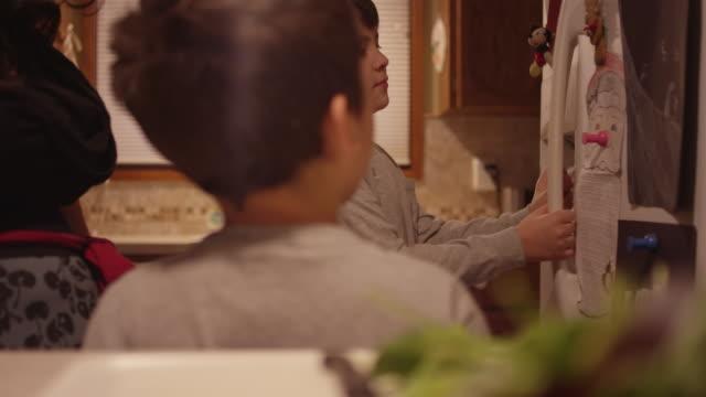 Un-niño-abre-el-refrigerador-en-la-cocina