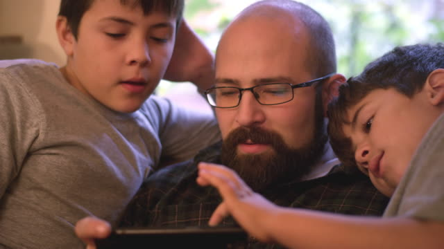 Two-boys-sit-with-their-dad-and-watch-him-use-his-phone
