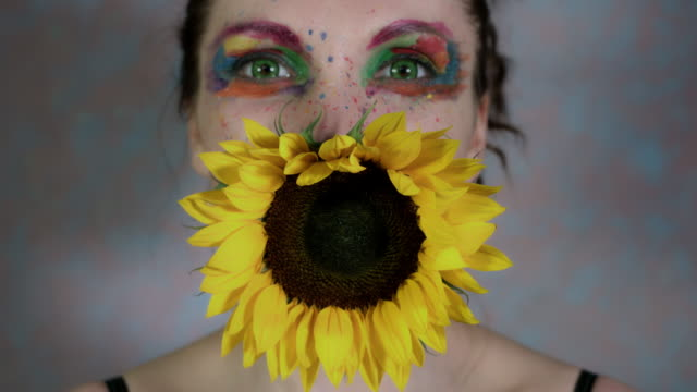 4k-Shot-of-a-Woman-with-Multicoloured-Make-up-With-Sunflower-(focus-on-flower)