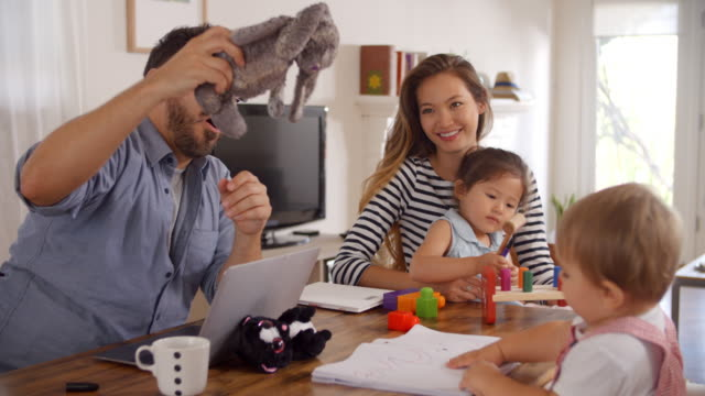 Father-Uses-Laptop-Whilst-Mother-Plays-With-Children-At-Home