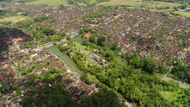 Aerial-view-in-Bali-Indonesia-:-Long-orderly-row-of-structures-with-tiered-thatched-roofs-at-Pura-Taman-Ayun-