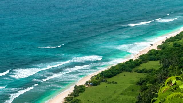 Turistas-que-llegan-a-la-solitaria-playa-de-arena-en-la-costa-de-Uluwatu-Bali-Indonesia