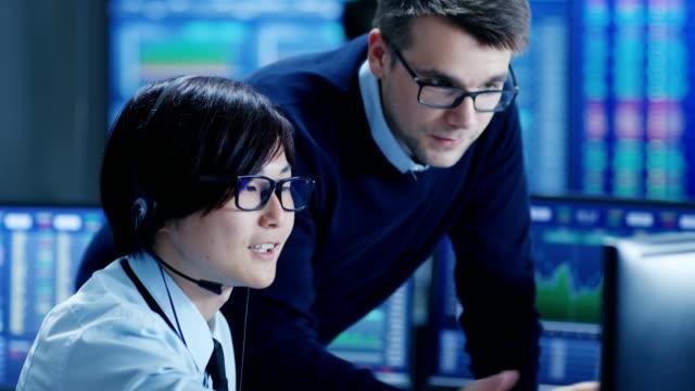 En-el-centro-de-operaciones-de-red-Senior-Trader-enseña-joven-asociado-a-hace-que-el-cliente-Personal-llamada-con-auriculares-Está-rodeados-por-los-monitores-que-muestran-datos-y-gráficos-