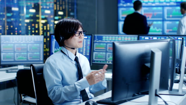 In-the-Network-Operations-Center-Trader-Makes-Personal-Client-Call-with-a-Headset-In-the-Background-Traders-Discuss-Data-Shown-on-Monitors-