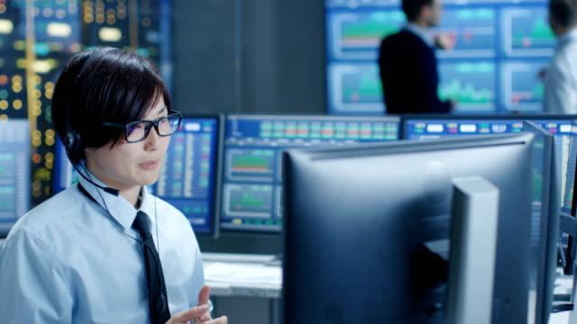 En-el-Network-Operations-Center-Trader-hace-cliente-Personal-llamada-con-auriculares-En-los-comerciantes-de-fondo-discutir-datos-que-se-muestran-en-los-monitores-