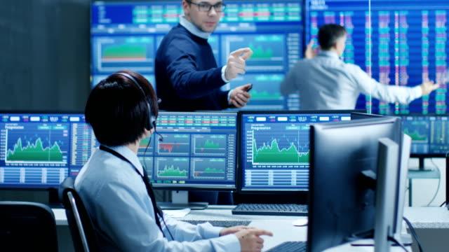 En-las-operaciones-de-red-Senior-Trader-dicta-números-de-Stock-a-su-operador-que-hace-llama-con-un-auricular-En-los-comerciantes-de-fondo-discutir-datos-que-se-muestran-en-los-monitores-
