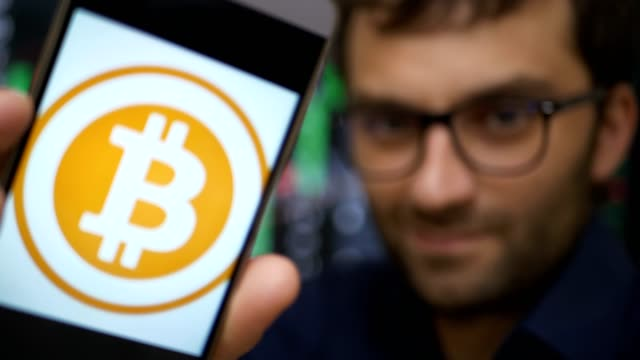 Man-earns-bitcoins-on-his-bitcoin-farm-Male-making-a-payment-with-bitcoins-cryptocurrency-using-his-smartphone-Custom-application-interface-design-Guy-smiles-earns-on-the-financial-market