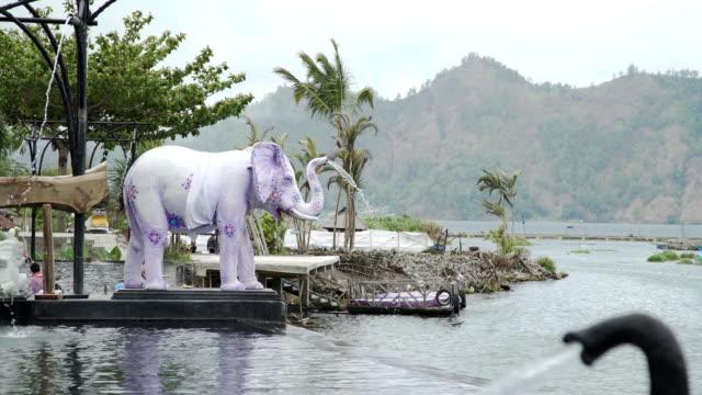 Agua-que-fluye-en-la-piscina-de-aguas-termales-de-tronco-de-estatuas-de-elefantes-Bali