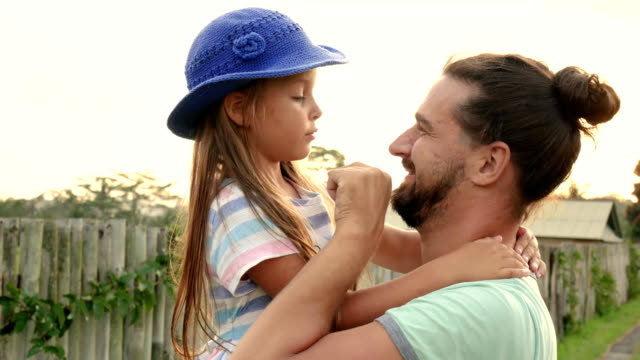 Father-having-fun-holding-his-little-daughter-in-arms