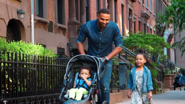 Father-pushing-buggy-walking-with-daughters-in-the-street