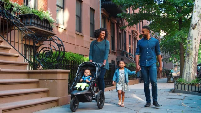 Young-black-family-with-stroller-walking-in-Brooklyn-street