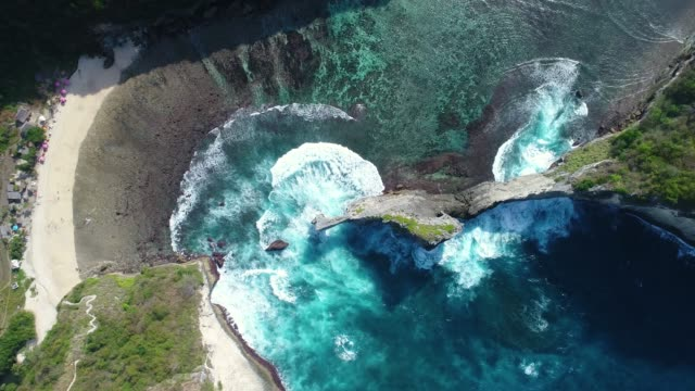 Aerial-view-by-drone-4k-camera-Rocks-in-a-blue-sea-lagoon-with-breaking-waves-