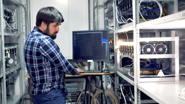 IT-engineer-working-in-cryptocurrency-mining-factory-Industrial-mining-farm-for-bitcoin-and-cryptocurrency-money-