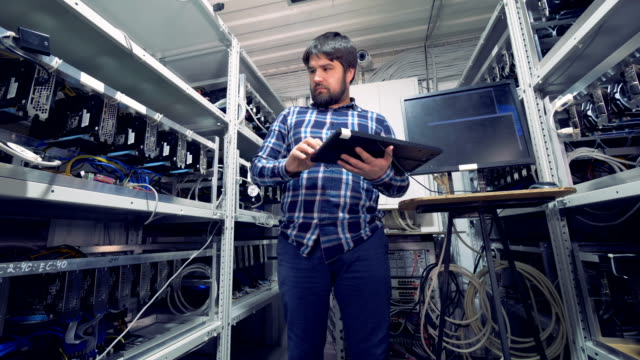 Cryptocurrency-mining-rig-with-a-male-miner-and-specialized-equipment-in-it