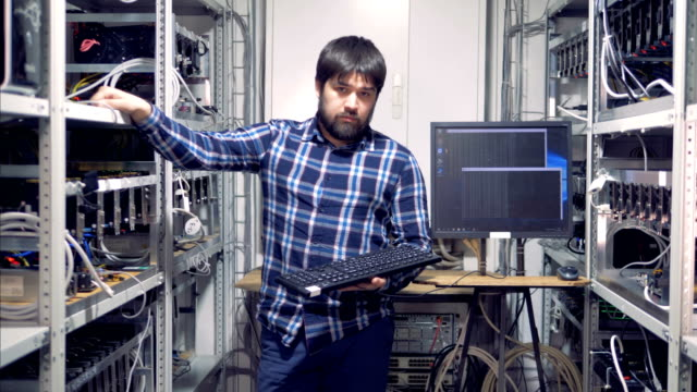 Cryptocurrency-mining-specialist-is-standing-in-a-mining-rig-unit-and-looking-into-the-camera