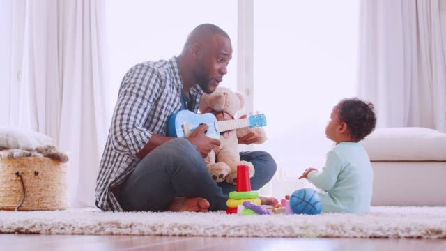 Young-black-father-playing-ukulele-with-son-in-sitting-room