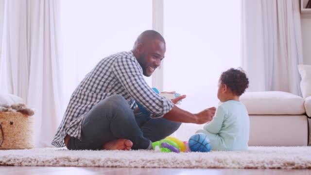Junge-schwarze-Vater-mit-Sohn-in-ihrem-Wohnzimmer-spielen