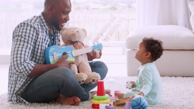 Joven-padre-negro-cantando-a-su-hijo-llorando-en-la-sala-de-estar