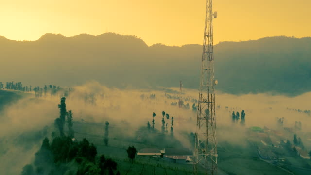 Mist-flowing-into-vast-landscapes-of-Mount-Bromo-at-sunset-an-aerial-view-indonesia