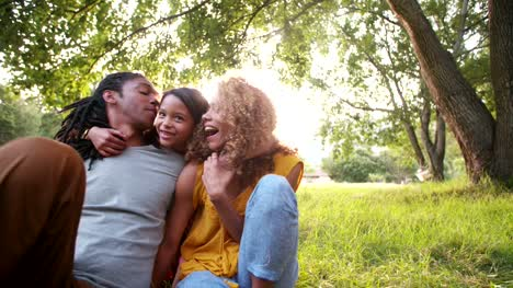 Young-African-American-family-laughing-and-smiling-with-their-cute-daughter