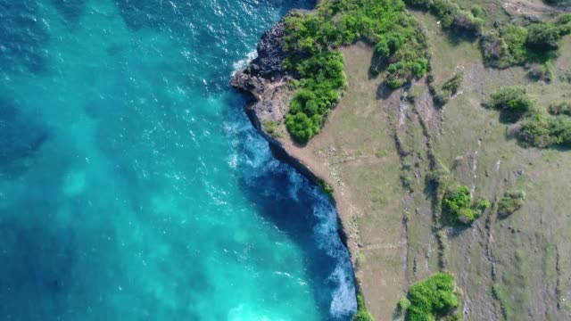 Cliff-with-waves-crashing-against-a-rocky-shore-Nusa-Penida-Indonesia-