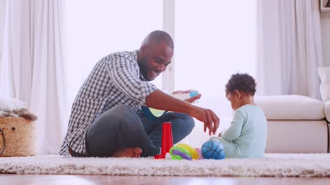 Young-black-father-playing-with-son-in-their-sitting-room