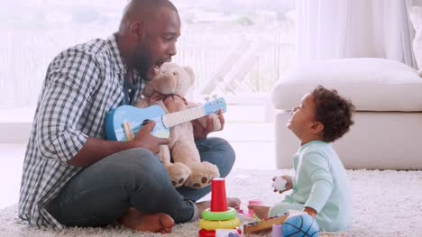 Young-black-father-singing-to-his-crying-son-in-sitting-room