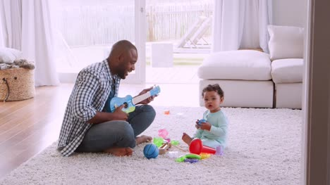 Young-black-father-singing-to-his-young-son-in-sitting-room