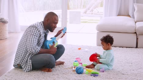 Young-black-father-playing-with-his-son-in-sitting-room