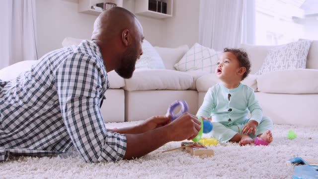 Young-black-father-lying-on-floor-playing-with-his-young-son