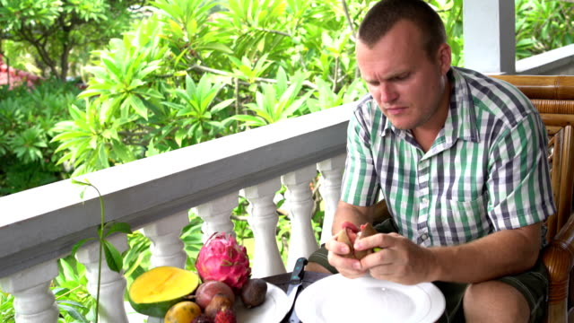 Man-sitting-on-the-balcony-cleans-the-mangosteen-fruit-and-eats