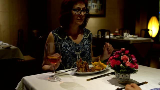 Mujer-sentada-en-una-mesa-en-el-restaurante-comer-hablar-chokaetsja-un-vaso-y-beber-vino-tinto