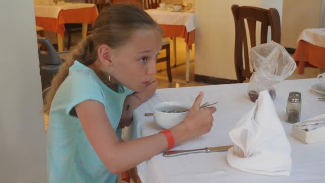 Adorable-girl-eating-porridge-from-bowl-for-breakfast-in-cafe