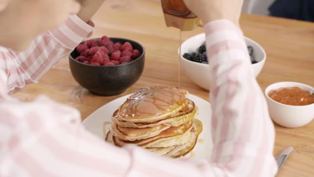 Part-of-woman-eating-pancake-at-kitchen